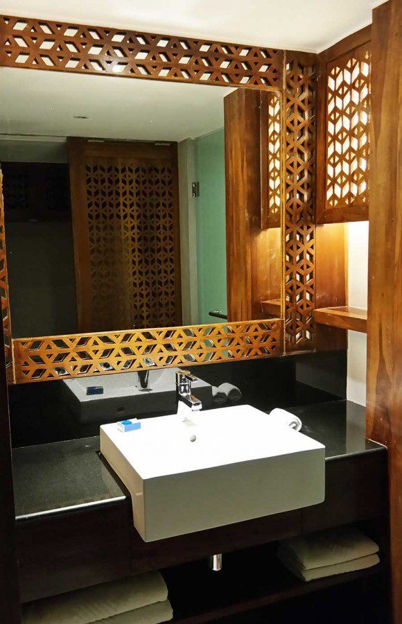 mix exotic design by framing a mirror with carved wood with modern sink and counter top